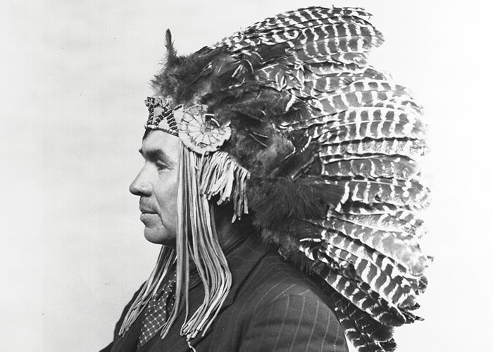 Binaaswi portant un costume rayé et une coiffe de plumes.