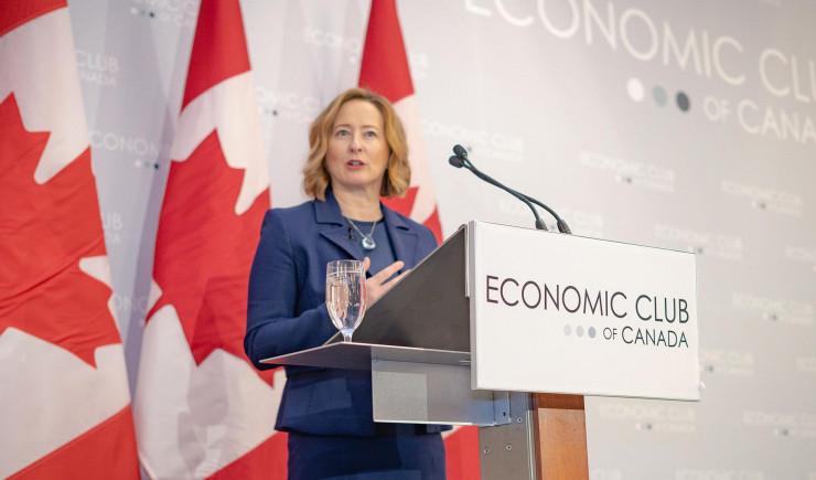 Carolyn Wilkins debout à un lutrin avec des drapeaux du Canada en arrière-plan.