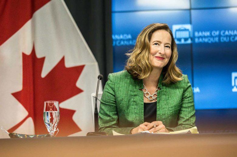 Carolyn A. Wilkins souriante et assise à une table pendant une conférence de presse à la Banque du Canada.