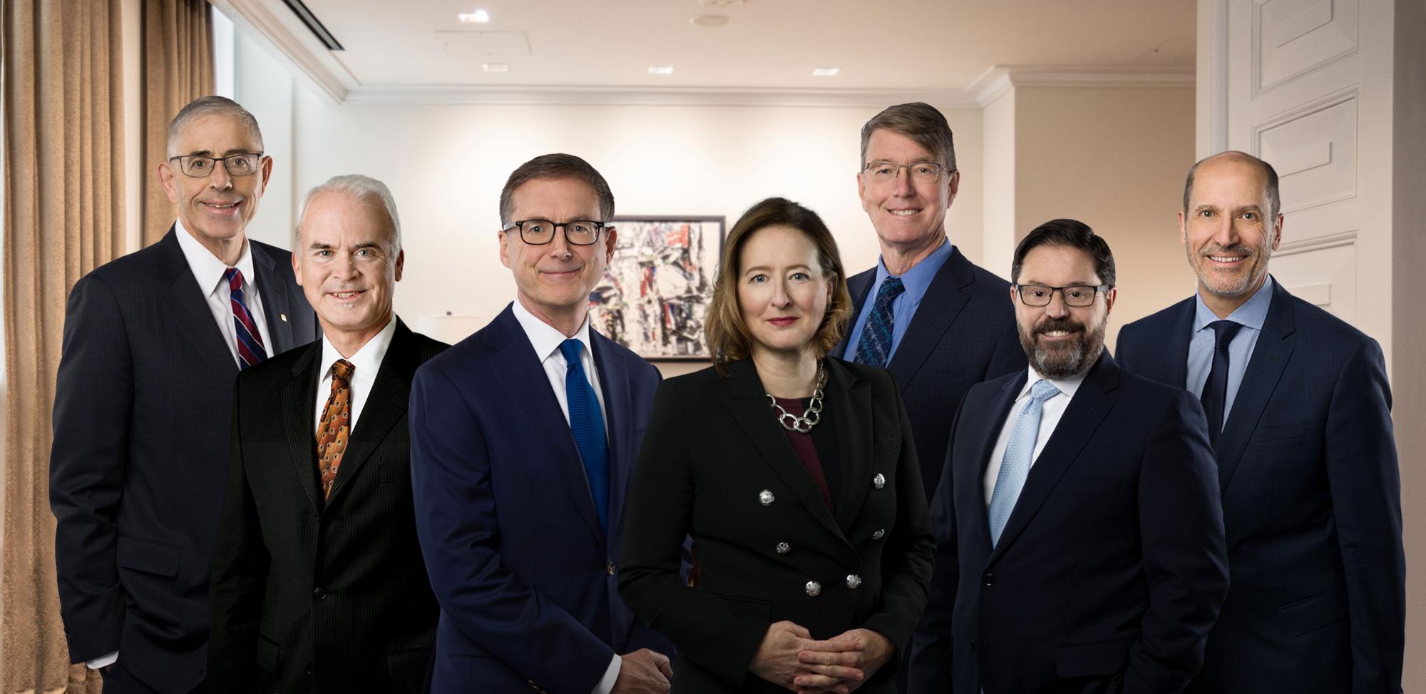 Les sept membres du Conseil de direction institutionnelle posant debout de façon solennelle devant une salle de réunion au siège.