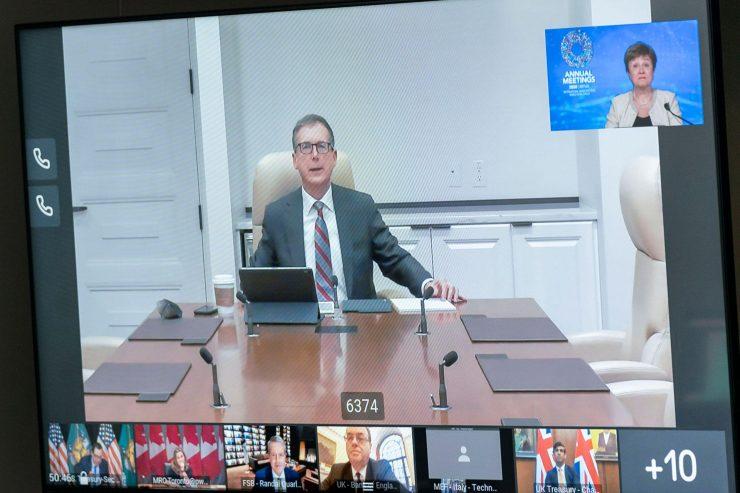 Saisie d'écran montrant le gouverneur Macklem assis à une table de conférence et participant à une réunion virtuelle